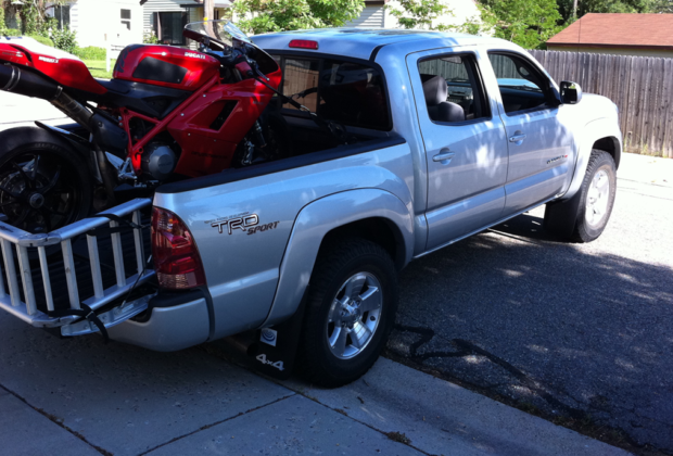 Load a motorcycle in the back of a truck